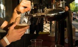 Het mannelijke barman gietende bier in een glasclose-up Straatvoedsel royalty-vrije stock afbeelding