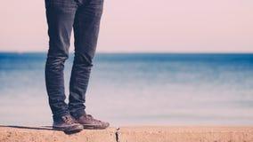 Het mannelijke benen lopen ontspannen door kust stock foto