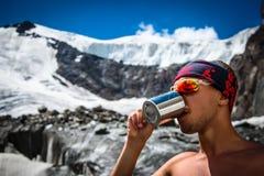 Het mannelijke bergbeklimmer drinkwater van een mok op een gletsjer in de bergen reist het avonturen actieve vakanties van het Le royalty-vrije stock afbeelding