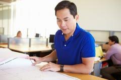 Het mannelijke Bureau van Architectenstudying plans in Stock Foto