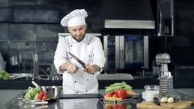 Het mannelijke chef-kok stellen bij professionele keuken Kok het spelen met het scherpen van messen stock footage