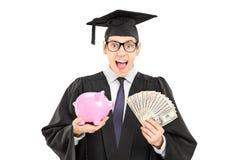 Het mannelijke die geld van de studentenholding en een piggybank op witte bac wordt geïsoleerd Royalty-vrije Stock Foto