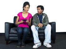 Het mannelijke en vrouwelijke vechten over een videospelletjecontrole Stock Afbeeldingen