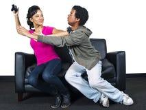 Het mannelijke en vrouwelijke vechten over een videospelletjecontrole Royalty-vrije Stock Foto