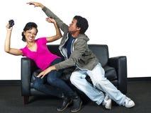 Het mannelijke en vrouwelijke vechten over een videospelletjecontrole Stock Foto