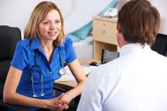 Het mannelijke geduldige spreken met vrouwelijke arts Stock Fotografie