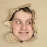 Het mannelijke gezicht kijkt omhoog van gat in karton Stock Foto
