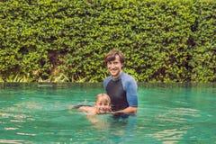 Het mannelijke instructeur zwemmen voor kinderen onderwijst een gelukkige jongen aan swi stock fotografie