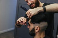 Het mannelijke kapper kammen en het scheren haar van een mannelijke cliënt stock foto's