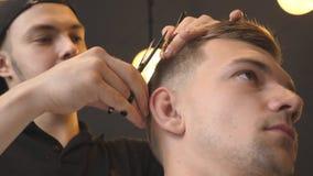 Het mannelijke kapper kammen en het snijden haar van jonge klant door haarborstel en schaar in salon Kaukasische kapper stock footage