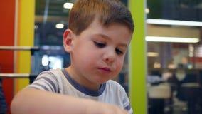 Het mannelijke kind eet hamburger en de Frieten met saus in snel voedselkoffie, kleine jongen eet met eetlust in kinderen stock videobeelden
