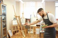 Het mannelijke kunstenaar schilderen in workshop stock afbeeldingen