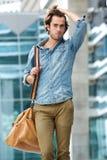 Het mannelijke model stellen met reiszak in openlucht stock foto's