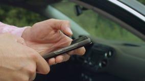Het mannelijke overseinen van de handentekst op cellphone dichtbij auto