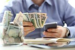 Het mannelijke pak van de handholding van bankbiljetten en cellphone die ??n of andere berekening maken die zijn toekomstige uitg stock foto's