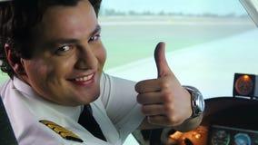 Het mannelijke proef glimlachen in cockpit, die duimen op handteken tonen, luchtvervoer stock video