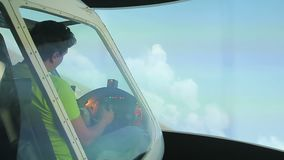 Het mannelijke proef leren om vliegtuigensimulator, het spelen videospelletje tijdens de vlucht te navigeren stock video