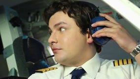 Het mannelijke proef spreken aan crewmember, coördinerende acties tijdens vlucht, groepswerk stock videobeelden