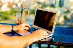 Het mannelijke typen op laptop in een koffie op het dak van high-rise met een mooi panorama van de stad, sluit omhoog royalty-vrije stock afbeelding