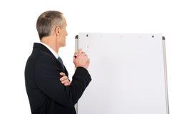 Het mannelijke uitvoerende schrijven op een flipchart Stock Foto's