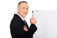 Het mannelijke uitvoerende schrijven op een flipchart Stock Foto