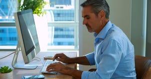 Het mannelijke uitvoerende spreken op mobiele telefoon terwijl het werken over computer bij zijn bureau stock footage