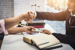 Het mannelijke van de advocaatmens en zakenman schudden overhandigt lijst na het bespreken van een contractovereenkomst rechtvaar stock afbeelding
