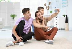 Het mannelijke vrolijke paar met bevordert zoon het nemen selfie Royalty-vrije Stock Afbeeldingen