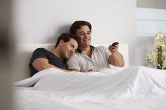 Het mannelijke vrolijke paar ontspant in bed samen lettend op TV royalty-vrije stock afbeelding