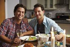Het mannelijke vrolijke paar thuis voor een romantisch diner kijkt aan camera royalty-vrije stock foto's