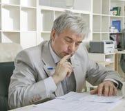 Het mannelijke werken op middelbare leeftijd met documenten Stock Foto