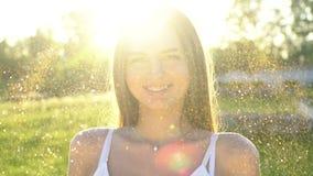 Het mannequinmeisje in gouden fonkelingen schittert stellend Het portret van mooie vrouw met schittert in openlucht confettien stock footage