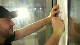 Het mannetje, bouwer onderzoekt zorgvuldig en trekt iets op het plan van flat stock videobeelden