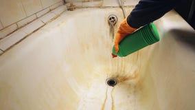 Het mannetje dient oranje rubberhandschoenen in giet een gel in de gootsteen om de ton en het toilet in de badkamers schoon te ma stock footage