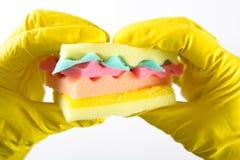 Het mannetje dient yelliw handschoenen in houdend een hamburger van sponsen verschillende kleuren die wordt gemaakt Concept ongez Royalty-vrije Stock Afbeeldingen