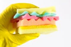Het mannetje dient yelliw handschoenen in houdend een hamburger van sponsen verschillende kleuren die wordt gemaakt Concept ongez Royalty-vrije Stock Foto