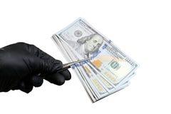 Het mannetje dient zwarte handschoen in houdt een pak Amerikaanse dollars met pincet Voorwerp voor het ontwerp van het concept sc stock fotografie
