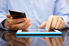 Het mannetje gebruikt slimme mobiele telefoon en tabletcomputer bij hetzelfde Royalty-vrije Stock Fotografie