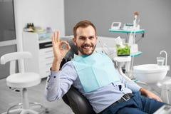 Het mannetje glimlacht aan de camera en toont o.k. teken die na tandenbehandeling worden tevredengesteld in een moderne tandheelk stock afbeeldingen