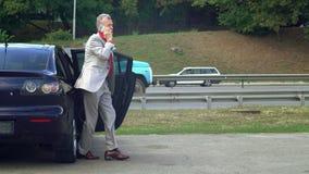 Het mannetje in jaren uit gekomen voertuig en spreekt op telefoon stock videobeelden
