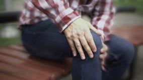 Het mannetje lijdt aan kniepijn, verwonde verbinding, artritis, vaag effect alsof pijn stock video