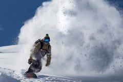 Het mannetje snowboarder boog en remmen die losse diepe sneeuw op de freeridehelling bespuiten stock foto's