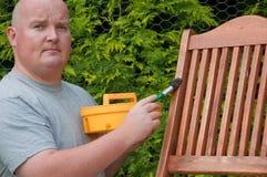 Het mannetje van de close-up buiten tuin het schilderen ligstoel stock foto