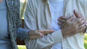 Het mannetje voelt plotseling scherpe pijn in zijn borst, vrouw die 911, noodsituatie draaien stock videobeelden