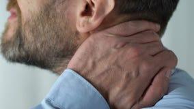 Het mannetje wat betreft hals, die sterke kramp hogere achter voelen, kneep zenuw, ongemak stock footage