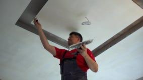 Het manusje van alles past pleister op plafond toe stock video