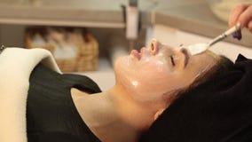 Het masker van de gezichtsschil, de behandeling van de kuuroordschoonheid, skincare Vrouw die gezichtszorg door schoonheidsspecia stock video