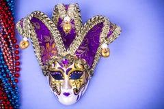 Het masker van festivalmardi gras en multicolored parels op heldere achtergrond stock fotografie