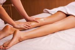 Het masseren van vermoeide spieren Stock Foto