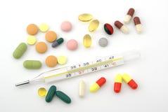 Het materiaal van de geneeskunde. Kwik thermometer en pillen Royalty-vrije Stock Foto's